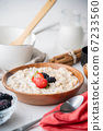 oatmeal with berries in wood bowl 67233560