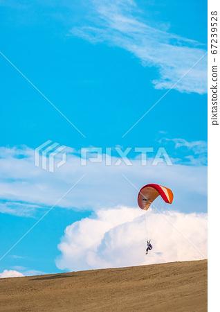年輕人在鳥取沙丘中享受滑翔傘 67239528