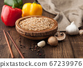 Wooden bowl with boiled long grain risotto rice 67239976