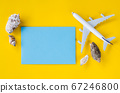Empty blue paper on yellow background with seashells and decorative airplane. Summer travel concept.  67246800