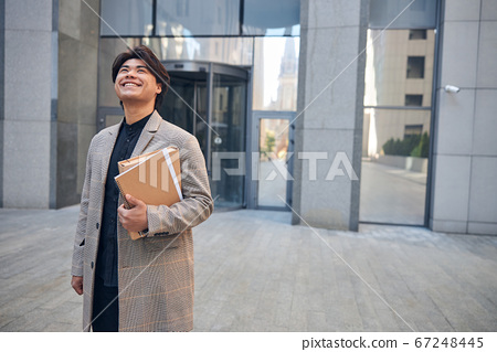 Cheerful young man with documents standing on the street 67248445