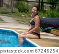 Laughing woman in black bikini sits alone with her feet in a residential swimming pool in natural light with copy space. 67249254