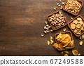 Delicious food to beer. Crackers, peanuts, pistachios and chips in square plates on brown wooden table 67249588