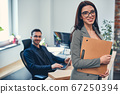 Smiling attractive woman wearing glasses holding folder paperwork in hand 67250394