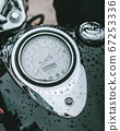 Black motorcycle tachometer covered in rain 67253336