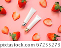 Natural skincare squeezing tube w/ fresh organic strawberries fruit on pink background. Packaging of eye cream, acne gel, lip scrub or hand cream. Cosmetic beauty product branding mock-up. Flat lay. 67255273
