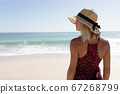 Woman wearing hat standing on the beach 67268799