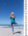 Senior Caucasian woman sitting on sand and practicing yoga 67268806