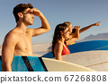 Multi-ethnic group of male and female, surfing on the beach 67268808