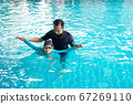Father teaching daughter to swim in a swimming 67269110