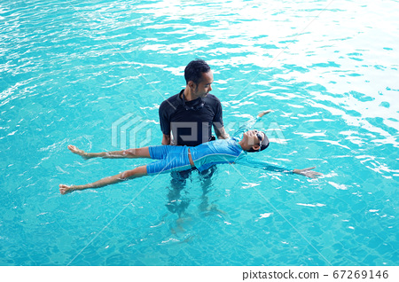 Father teaching daughter to swim 67269146