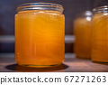 Golden yellow honey in glass jar on wooden board Closeup Copy space comp frame empty textspace 67271263