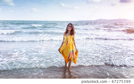 woman walking on the beach in summer with homemade 67275399