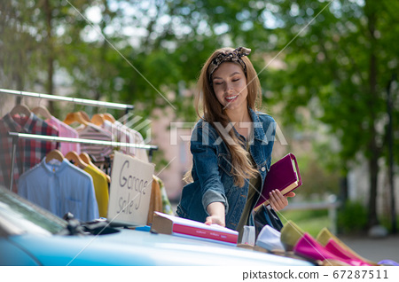 Pleasant young woman taking a book from the car 67287511