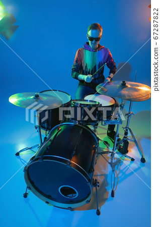 Young caucasian musician playing on gradient background in neon light. Concept of music, hobby, festival 67287822