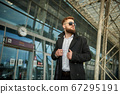 Red-head guy in sunglasses adjusting collar with both hands, man looking away 67295191