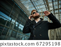 Urban business man in sunglasses talking smart phone traveling walking outside 67295198