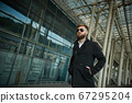Success. Stylish young bearded man in coat, sunglasses businessman standing 67295204
