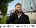 Urban business man talking smart phone traveling walking outside airport 67295207