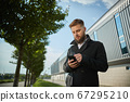 Urban business man talking smart phone traveling walking outside airport 67295210