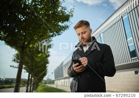 Urban business man talking smart phone traveling walking outside airport 67295210