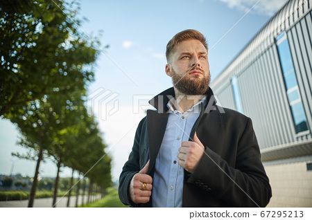 Portrait of seductive young man holding black jacket collar while standing 67295213