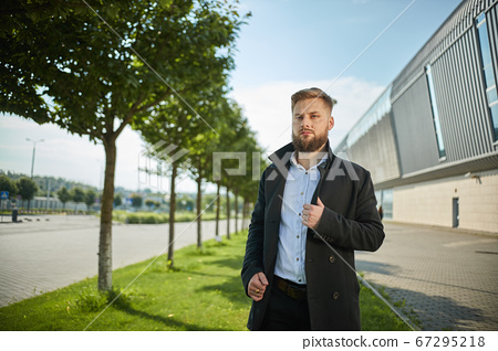 Portrait of seductive young man holding black jacket collar while standing 67295218