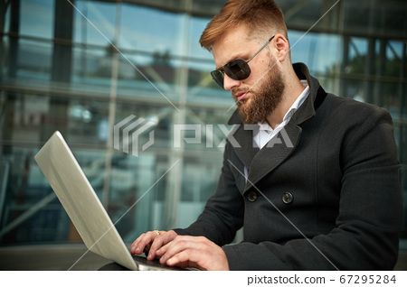 Manager holding laptop, Out of office work, young 67295284