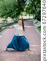 Portrait of charismatic girl with dreadlocks, wearing long blue skirt and white t-shirt, posing to camera standing in a city park alley with her arms and legs outstretched 67297640