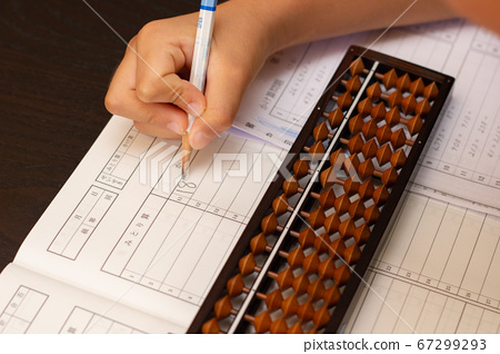A state where the answer calculated by the abacus is entered in a notebook 67299293