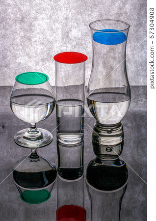 Still life with glass goblets with reflection on a gray background 67304908