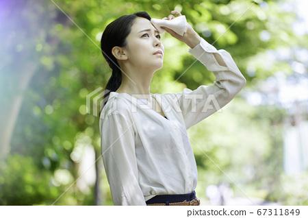 站立的少婦在夏天陽光下拿著手帕 67311849