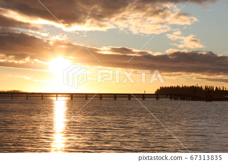 Woman crossing the bridge leading to the island with sunset background 67313835