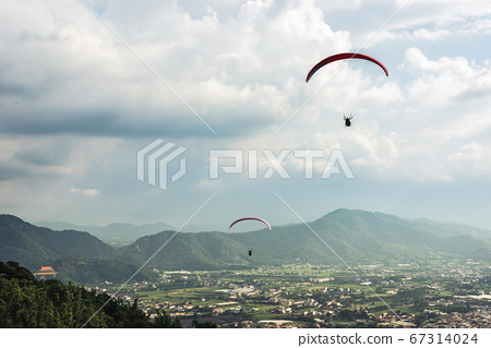 colorful paragliding over blue sky at town 67314024