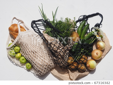Place for text.Bread and agricultural products, vegetables in knitted bags on a white background. No plastic. 67316382