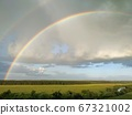 Rainbow and clouds over fields and river, smart 67321002