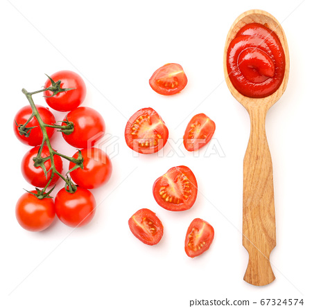 Ketchup in a spoon and cherry tomatoes on a white 67324574