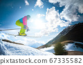 Girl skier in flight after jumping from a kicker in the spring against the backdrop of mountains and blue sky. Close-up wide angle. The concept of closing the ski season and skiing in spring 67335582