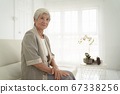 Smiling senior woman sitting on sofa and looking 67338256