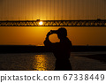 Silhouette of a woman shooting the sunset over the Akashi Kaikyo Bridge in Higashi Maiko Town, Tarumi Ward, Kobe City, Hyogo Prefecture with a smartphone 67338449