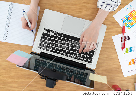 觸摸筆記本電腦鍵盤時在筆記本上記筆記的年輕女子的免提臉 67341259