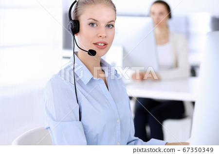 Call center office. Beautiful blonde woman using computer and headset for consulting clients online. Group of operators working as customer service occupation. Business people concept 67350349