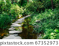 Stone path with green forest along the stream at Semiwon garden in Yangpyeong, Korea 67352973