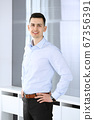 Businessman standing and looking at camera in office. Headshot of casual dressed guy 67356391