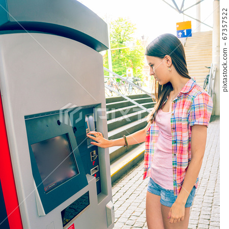 Young woman uses a vending machine for transport 67357522