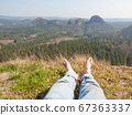 Legs of traveler sitting on top of mountain 67363337