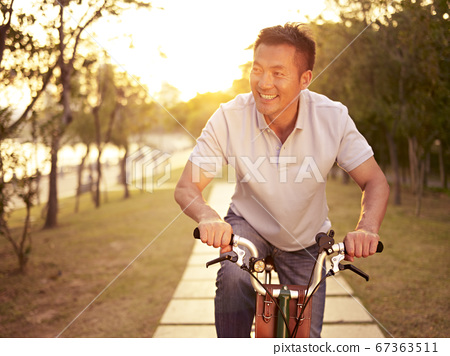 mid-adult asian man riding bicycle outdoors at sunset, smiling and happy 67363511