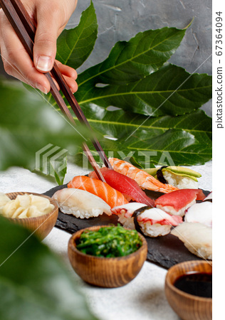 Close up of hand taking suchi with chopsticks from 67364094