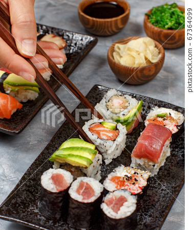 Close up of hand taking roll with chopsticks from 67364099