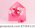 Pink envelope full of flowers  over a pink 67364114